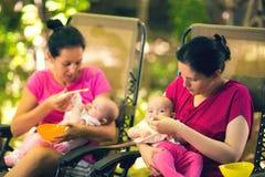 2 женщины подавая младенцам еда к младенцу Стоковые Изображения RF