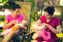 2 женщины подавая младенцам еда к младенцу Стоковая Фотография RF