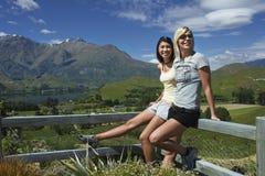 2 женщины полагаясь против загородки сельской местности Стоковое фото RF