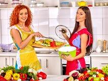 Женщины подготавливая vegetable еду на кухне Стоковые Изображения
