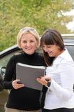 2 женщины подписывая контракт для того чтобы купить автомобиль Стоковое Фото