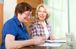 2 женщины подписывая документы дома Стоковые Изображения