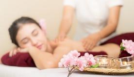 Женщины получают задний массаж расплывчатый с свечами курорта Стоковая Фотография