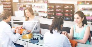 Женщины получая их ногти сделанный на салоне красоты Стоковые Фото