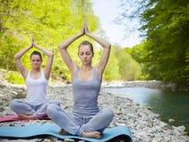 2 женщины практикуют йогу рекой горы Стоковая Фотография