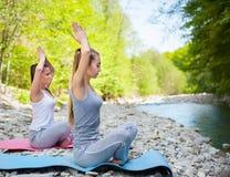 2 женщины практикуют йогу рекой горы Стоковое фото RF