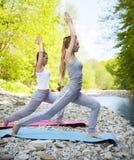 2 женщины практикуют йогу рекой горы Стоковая Фотография RF