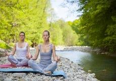 2 женщины практикуют йогу рекой горы Стоковые Фото