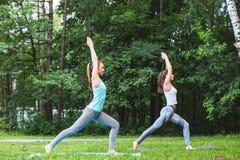 2 женщины практикуя йогу в парке Стоковое фото RF