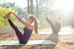 2 женщины практикуя йогу в древесине Стоковые Изображения