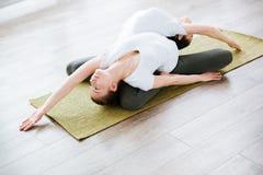 2 женщины практикуя йогу в студии Стоковое Изображение