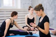 Женщины практикуя йогу на оздоровительном клубе Маленькие девочки говоря и ослабляя после фитнеса, инструктора йоги говорят на Стоковые Изображения
