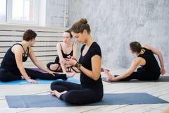 Женщины практикуя йогу на оздоровительном клубе Маленькие девочки говоря и ослабляя после фитнеса, инструктора йоги говорят на Стоковое фото RF