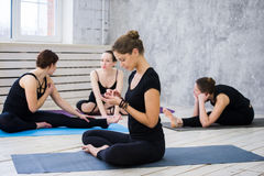 Женщины практикуя йогу на оздоровительном клубе Маленькие девочки говоря и ослабляя после фитнеса, инструктора йоги говорят на Стоковые Изображения RF