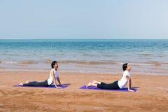 Женщины практикуя йогу на пляже стоковое фото