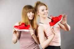 2 женщины представляя тренерам sportswear ботинки Стоковое Изображение RF