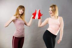 2 женщины представляя тренерам sportswear ботинки Стоковая Фотография