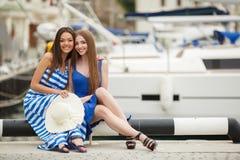 2 женщины представляя в яхтах гавани на заднем плане Стоковое Фото