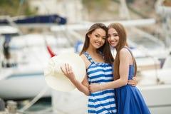 2 женщины представляя в яхтах гавани на заднем плане Стоковое Изображение RF