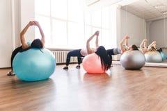 Женщины пригонки разрабатывая на шариках в студии фитнеса стоковое фото rf