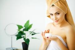 Женщины прикладывают сливк и лосьон к ее стороне после купать внутри стоковая фотография rf