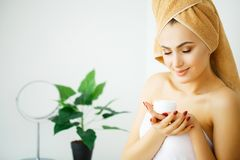 Женщины прикладывают сливк и лосьон к ее стороне после купать внутри стоковые фото