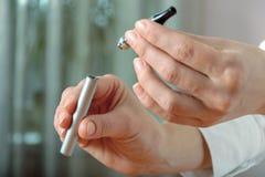 Женщины прикрепили часть электронной сигареты Стоковая Фотография