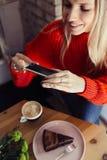 Женщины принимая фото еды по умному телефону стоковые фотографии rf