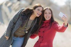 Женщины принимая фото с мобильным телефоном Стоковые Фото
