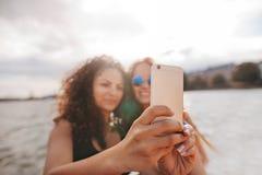 Женщины принимая selfie с умным телефоном озером Стоковая Фотография