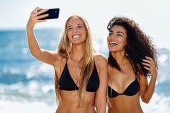 2 женщины принимая selfie фотографируют с smartphone в пляже Стоковое Изображение RF