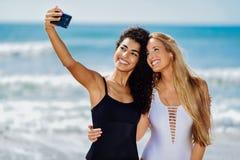 2 женщины принимая selfie фотографируют с smartphone в пляже Стоковое Фото