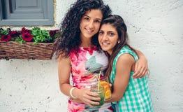 2 женщины при напитки смотря обнимать камеры Стоковое Изображение RF