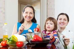 Женщины при ребенок варя обед veggie Стоковая Фотография RF