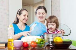 Женщины при ребенок совместно варя обед veggie Стоковое Фото