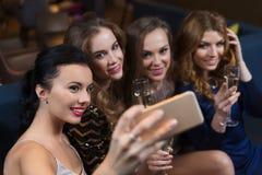 Женщины при шампанское принимая selfie на ночной клуб Стоковые Фотографии RF
