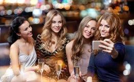 Женщины при шампанское принимая selfie на ночной клуб Стоковые Фото
