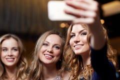 Женщины при smartphone принимая selfie на ночной клуб Стоковое фото RF