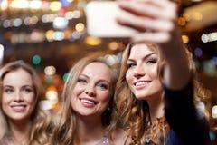 Женщины при smartphone принимая selfie на ночной клуб Стоковые Изображения