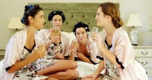 4 женщины провозглашать стекла шампанского на кровати 4K 4k акции видеоматериалы