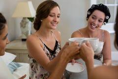 Женщины провозглашать чашка чаю в спальне Стоковая Фотография RF