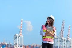 Женщины проектируют держать компьтер-книжку и работу с кораблем перевозки груза контейнера в верфи на сумраке для логистического  стоковые фотографии rf