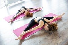 2 женщины протягивая и ослабляя в центре йоги Стоковые Фото