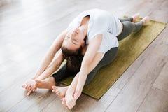 2 женщины протягивая и практикуя йогу в студии Стоковое фото RF