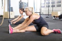 2 женщины протягивая на спортзале фитнеса Стоковые Фотографии RF