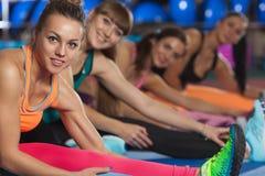 Женщины протягивая ноги в спортклубе Стоковые Изображения