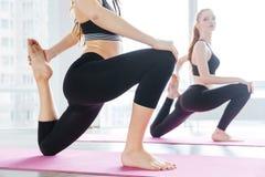 2 женщины протягивая barefoot на розовой циновке йоги Стоковые Фото