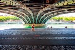 2 женщины проходя под мост около реки Стоковое Изображение RF