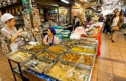 Женщины продают азиатский фаст фуд с мясом внутри рынка с деликатесами и продуктами сельского хозяйства Стоковые Фотографии RF