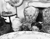 2 женщины пряча за таблицей и рассматривая край (все показанные люди более длинные живущие и никакое имущество не существует supp Стоковые Фотографии RF